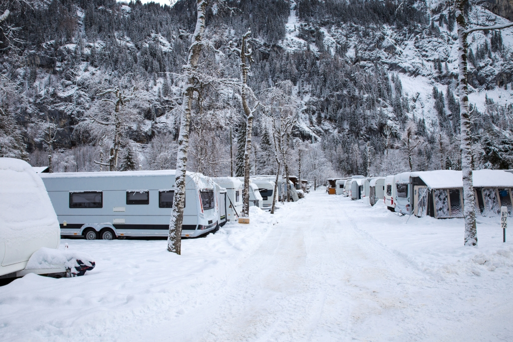 Winter camping with caravan. Camp site in the snow. Camping and